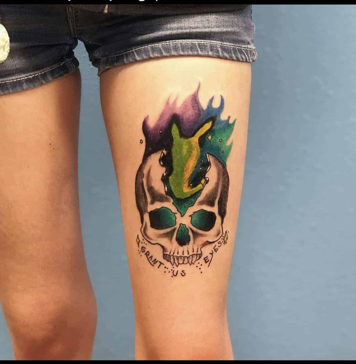 color flaming skull tattoo on thigh
