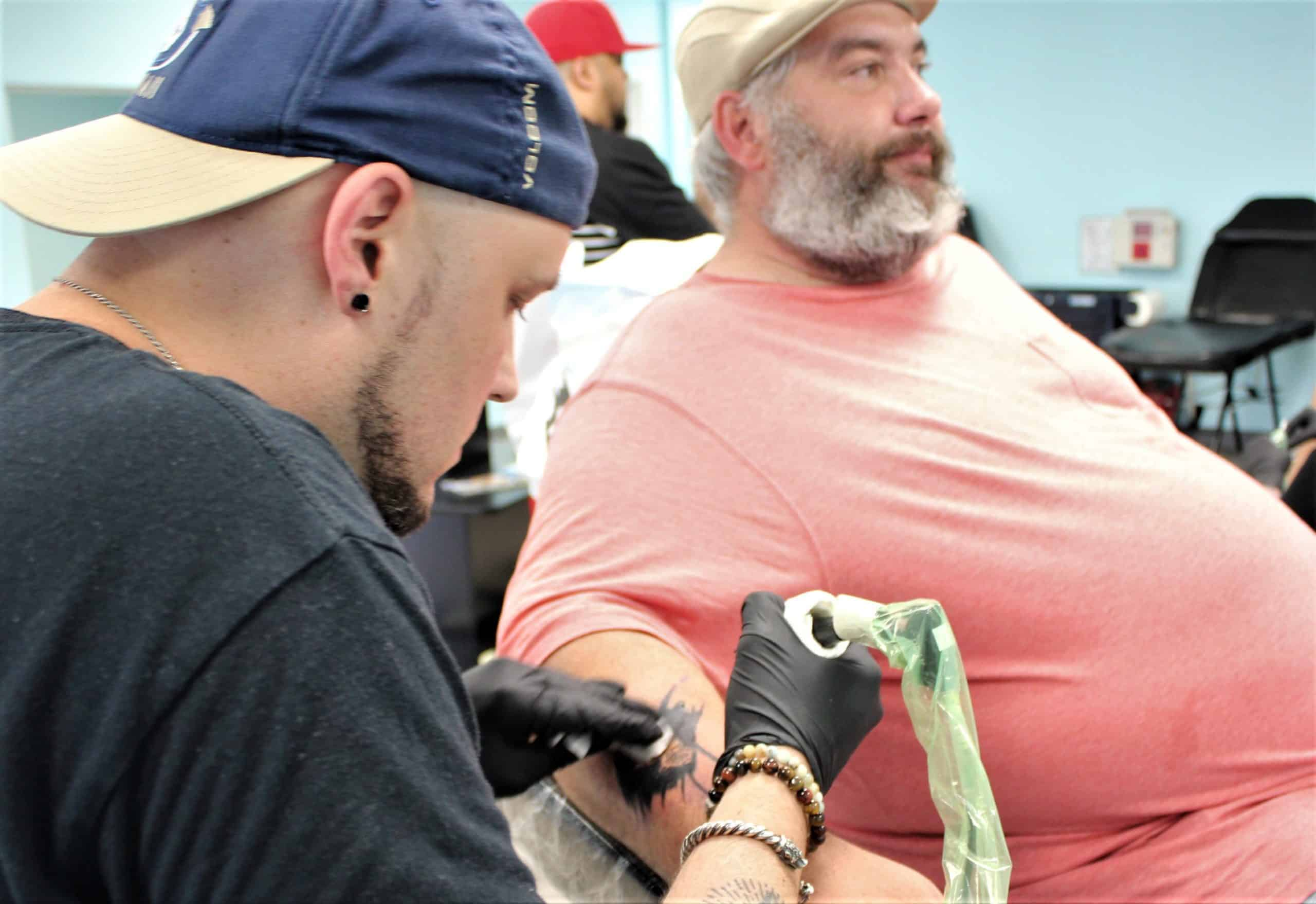 student tattooing arm