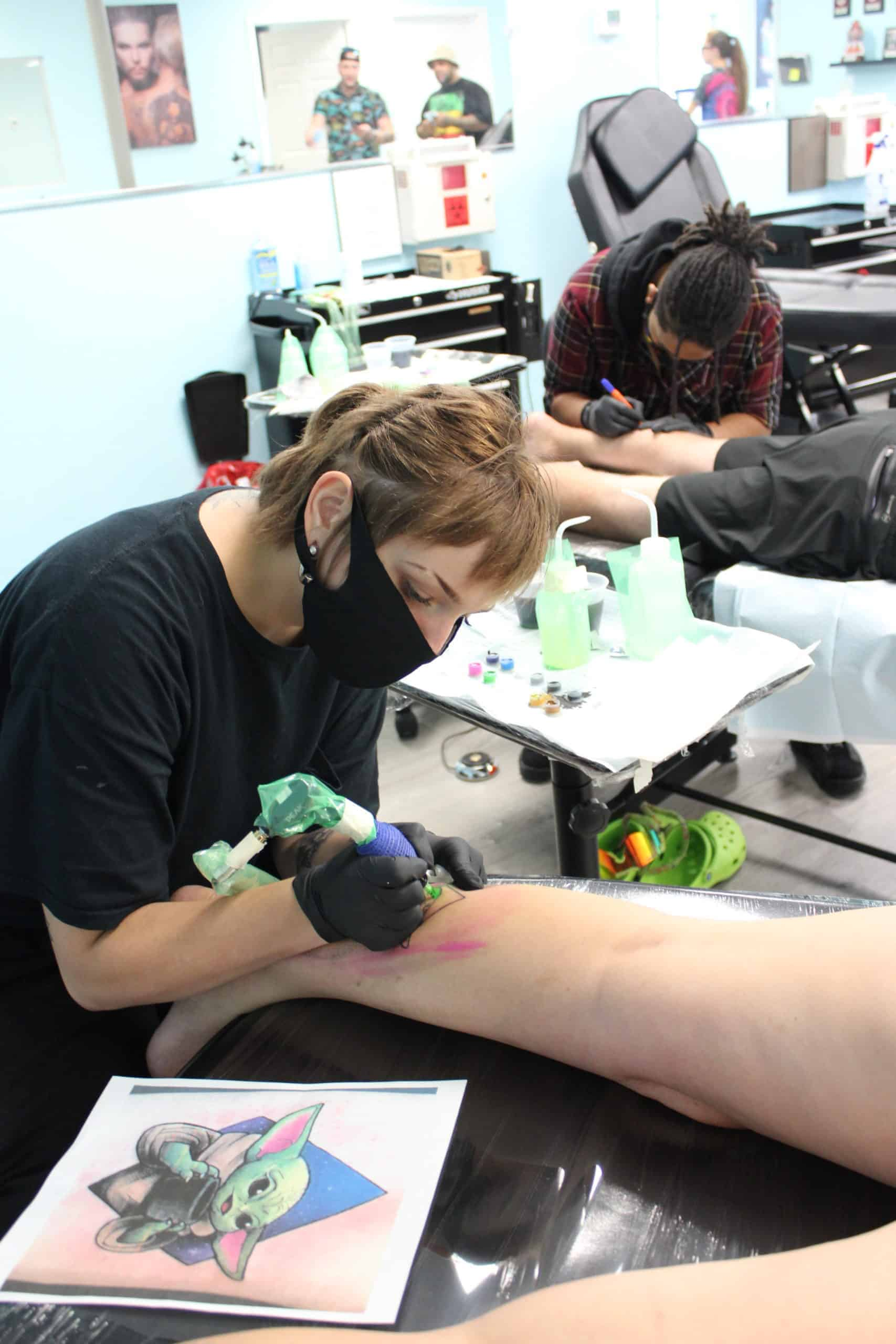 tattoo student working on tattooing calf