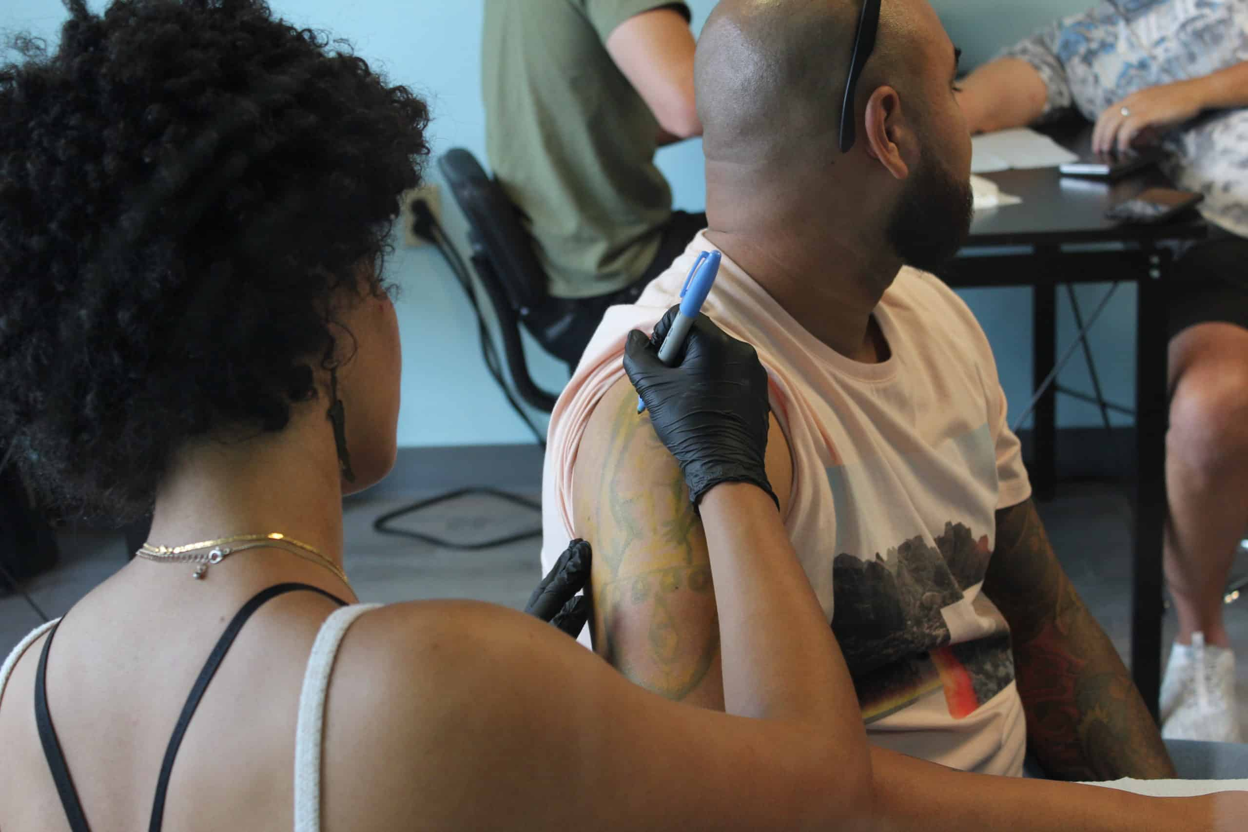 tattoo student outlining upper arm for tattoo