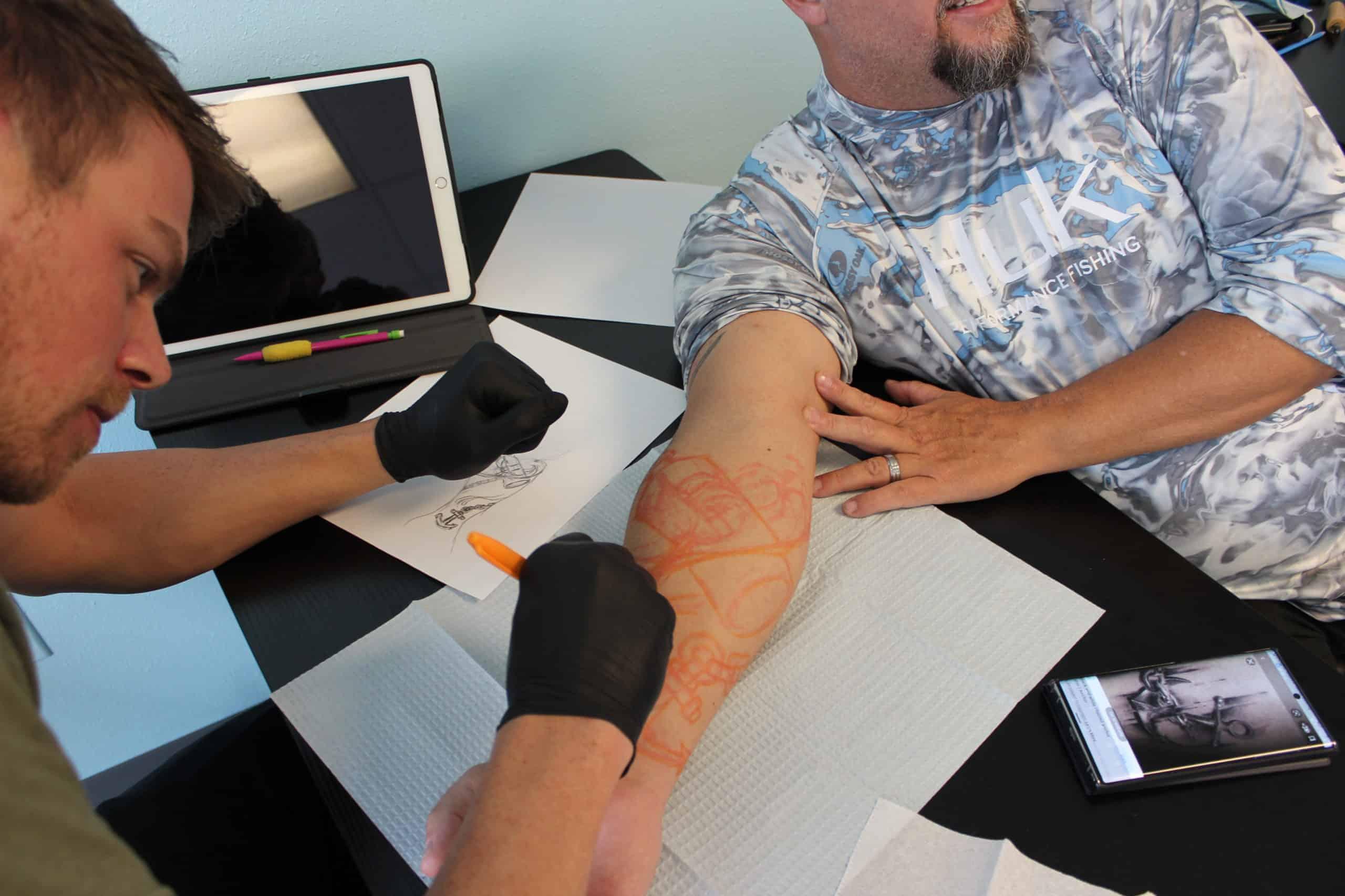 artist outlining tattoo